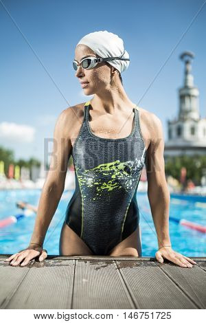 Sportive girl in the swimming pool outdoors. She wears a multi-colored swimsuit, a white swim cap and swim glasses. Woman looks to the right and lifted on hands on the pool side. Vertical.