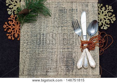 Vintage silverware on wooden background with Christmas decoration.