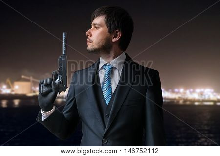 Agent Or Hitman Holds Pistol With Silencer In Hand At Night.