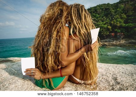 Young adult girls with flyers on tropical beach