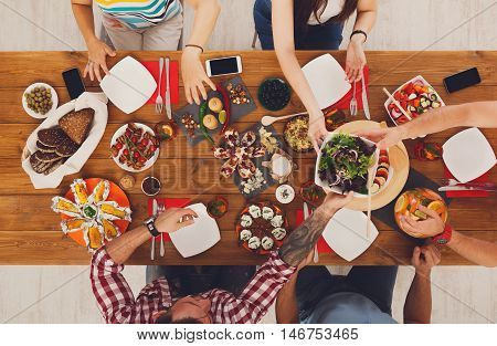 People eat healthy meals at festive table served for party. Friends celebrate with organic food on wooden table top view. Happy company having lunch, taking salad dish