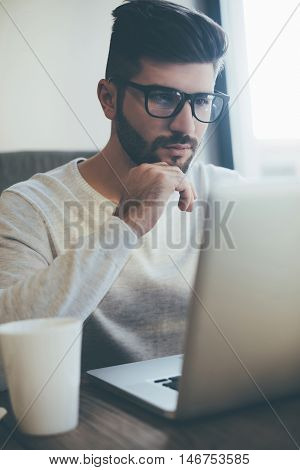 Thinking about solution. Thoughtful young man in glasses working on laptop and holding hand on chin while sitting in office or cafe