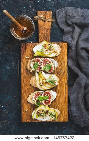 Crostini with pear, ricotta cheese, honey, figs, nuts and herbs. Breakfast toasts or snack sandwiches on rustic wooden board over dark blue grunge plywood background. Top view, vertical composition