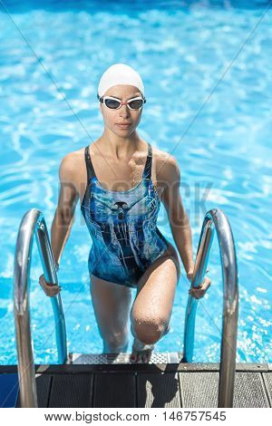 Attractive sportive girl stands on the pool ladder in the swim pool and holds hands on it. She wears a blue-black swimsuit, a white swim cap and swim glasses. Woman looks into the camera with a smile.