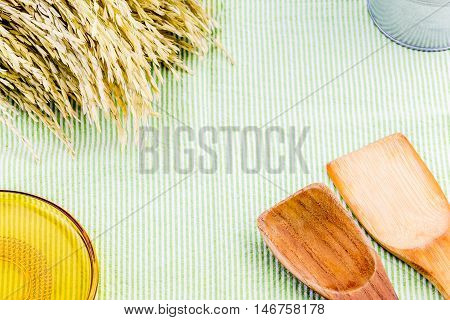 Top View Of Wooden Spoon, Yellow Glass Plate And Ear Of Rice On Table With Green Tablecloth, Copy Sp