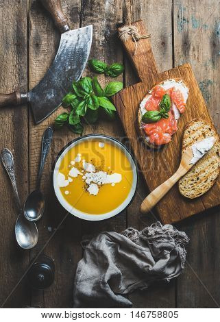 Dinner or lunch with pumpkin cream soup and salmon, ricotta and basil toasts over old rustic wooden background, top view, vertical composition