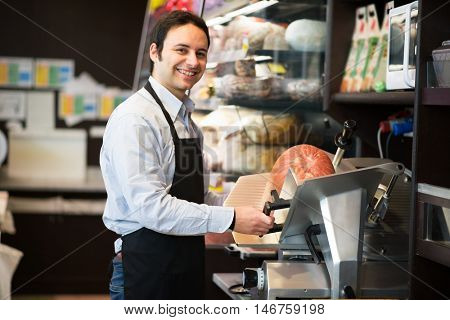 Shopkeeper cutting Italian sliced meat in a grocery store