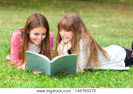 Girls reading a notebook together while lying down on the grass