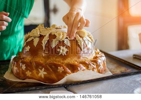 Lady's hand touches decorated pastry. Bread on oven tray. Professional baker makes wedding bread. Dish for a ceremony.