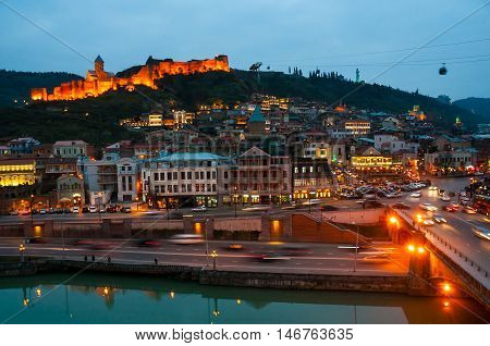 Aerial night view of Old Tbilisi Georgia with illuminated castle at the background