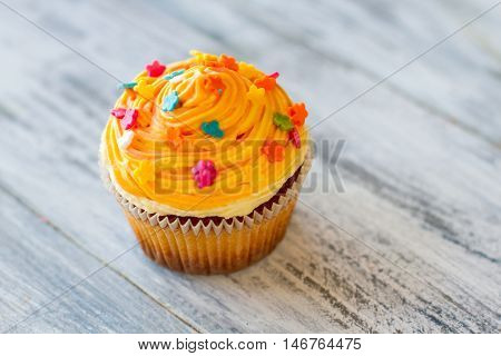 Cupcake with colorful decoration. Dessert on wooden surface. Colors of energy. Appetite and pleasure.