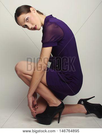 Fashion model wearing dress. Posing in studio.