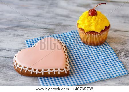 Heart biscuit and yellow cupcake. Pastry on checkered napkin. Surprise for those you love. Find an occasion for holiday.