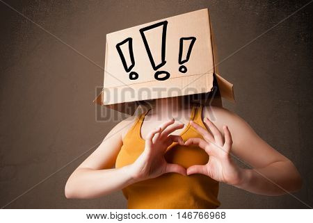 Young lady standing and gesturing with a cardboard box on her head with exclamation point
