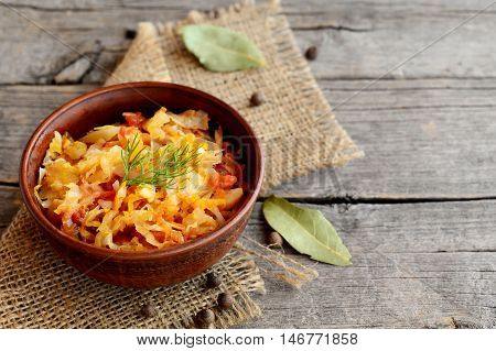 Braised cabbage in a bowl and on old wooden background. Cabbage braised with carrots, tomatoes and garlic and garnished with a sprig of dill. Vegetable dish