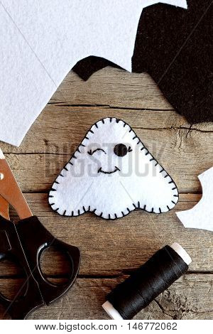 Cute felt Halloween ghost toy, scissors, black thread, scraps of felt on old wooden background. Supplies for ghost toy sewing. Halloween craft idea for kids. Closeup. Top view