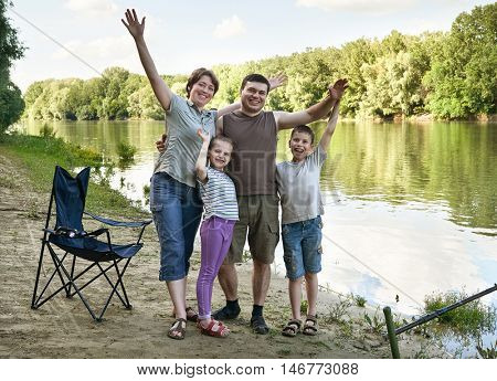 people camping and fishing, family active in nature, fish caught on bait, river and forest, summer season