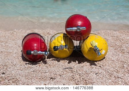 Red And Yellow Scuba Oxygen Tanks For Divers On A Beach