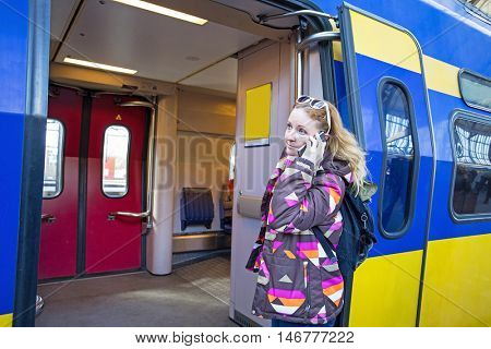 Young native dutch woman calling at the train station in Amsterdam Netherlands