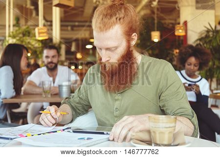 Portrait Of Young Redhead Freelancer With Long Beard Holding Pencil, Hand Drawing Schemes And Graphi