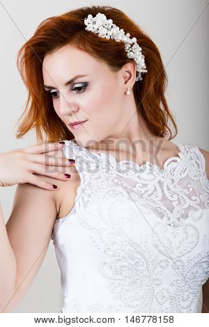 red-haired bride in a wedding dress holding wedding bouquet, bright unusual appearance. Beautiful wedding hairstyle and bright make-up.