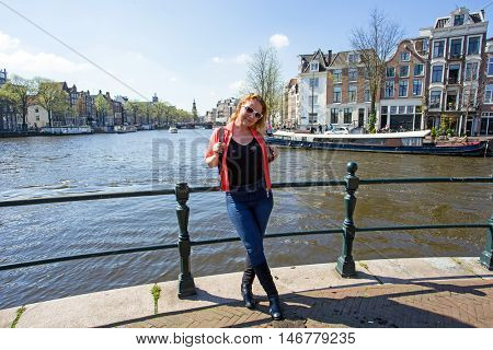 Dutch woman on a medieval bridge in Amsterdam the Netherlands