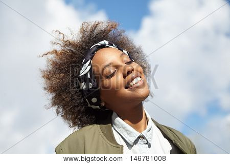 Close Up Shot Of Young Black Hipster Student Wearing Do-rag On Her Head, Smiling And Closing Her Eye