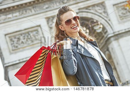 Smiling Woman With Shopping Bags In Paris Looking Into Distance