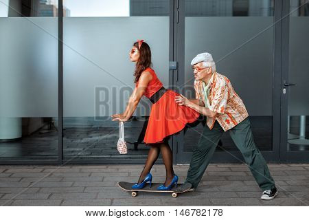 Old man pushing a woman on a skateboard.