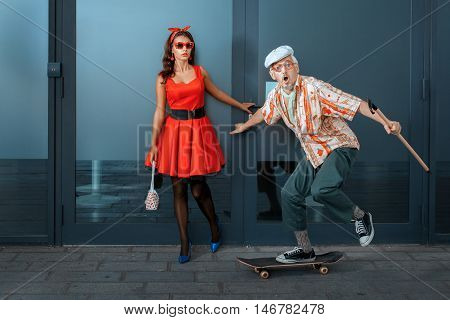 Old man with a cane to skateboard next to a young girl.
