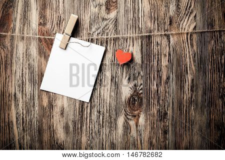 Blank instant photo and small red paper heart hanging on the clothesline On old wood texture background