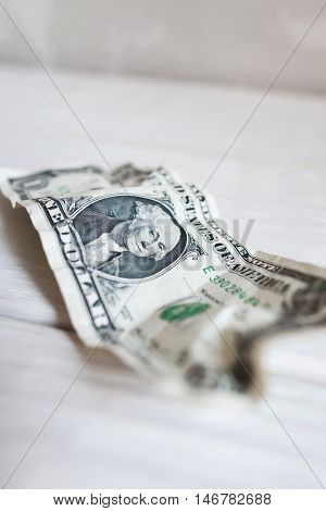 Worn crumpled one dollar bill, blurry, close-up. Old banknote of american money. Used buck. Finance, currency, devaluation concept