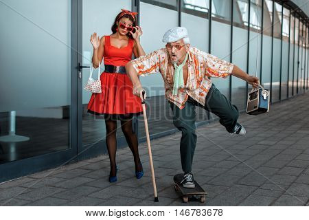 Old man ridiculously rides a skateboard the woman has opened a mouth from surprise.