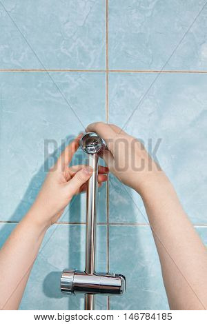 Close-up handyman hands install vertical holder for shower on wall.