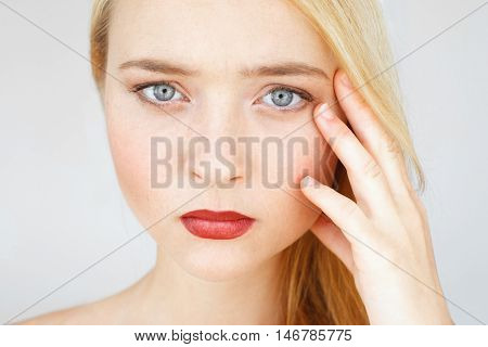 Serious pensive red-haired woman looking at camera. Young beautiful girl with headache touching her head and angrily looking at camera