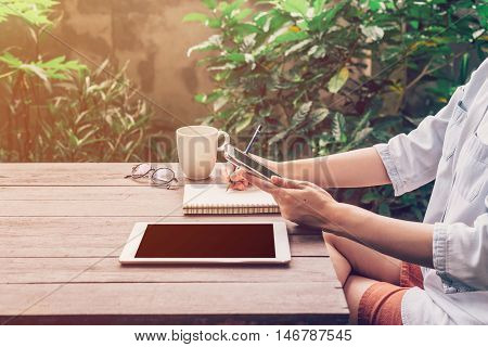 Woman Using Phone On Table Wood In Garden At Coffee Shop With Vintage Toned.