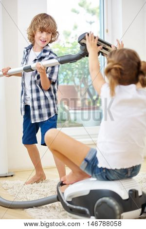 Boy and girl playing with vacuum cleaner while doing housecleaning