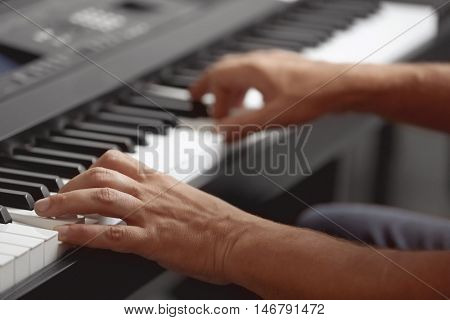 Male hands playing on synthesizer