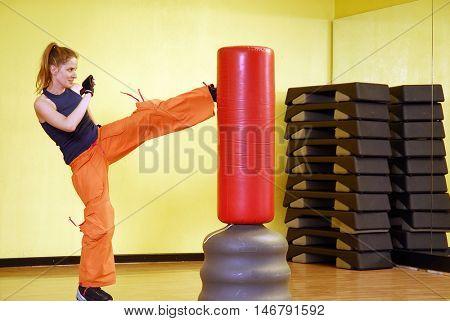 training fitness woman kicking punching bag.