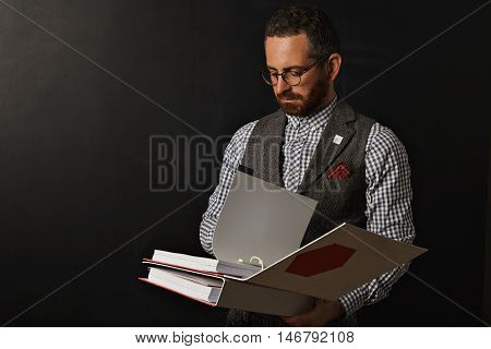 Hip young serious teacher in checkered shirt and tweed vest standing at a blank blackboard and reading from a thick bright red and white binder