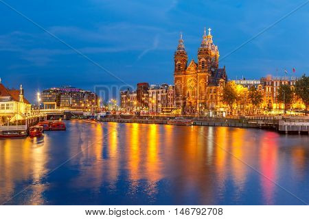 Night panoramic city view of Amsterdam canal, bridge and Basilica of Saint Nicholas, Holland, Netherlands. Long exposure.