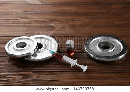 Dope in sports. Dumbbells and syringe on wooden background