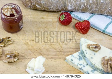 Cheese roquefort and brie, bread, jam, nuts and strawberries as background
