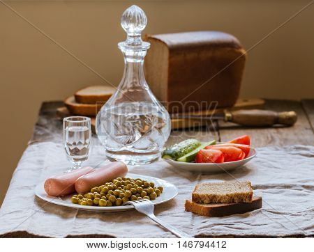Canned green peas and sausage on the white plate with bread and vodka  on linen tablecloth background