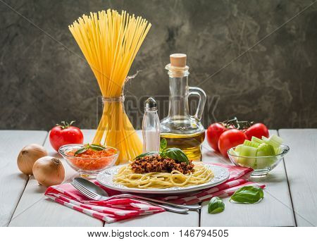 Spaghetti bologneseon white plate with ingredients on table