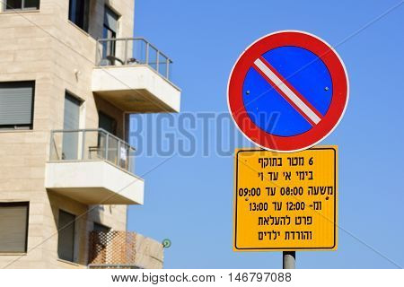 No parking sign in residential area in Tel Aviv that prohibits parking in certain hours.