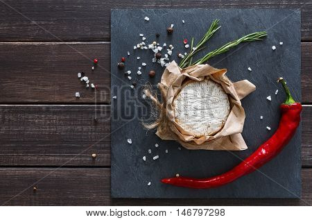 Cheese delikatessen closeup with chili pepper on black stone surface and wood. Camembert or brie circle in brown kraft paper decorated with basil, top view image