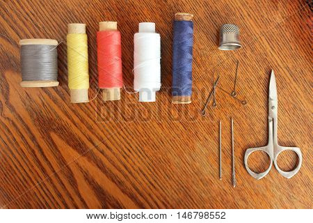 Sewing tools and accessories isolated on wood texture background spools of threads different colors, thimble, pins, needles, scissors