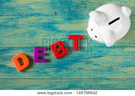 White piggy bank with a word DEBT made from plastic letters