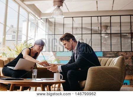 Two People Sitting In Office Lobby Using Mobile Phone